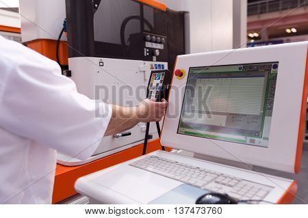 Technician working with computer numerical control (CNC) programmable machine. CNC technology.