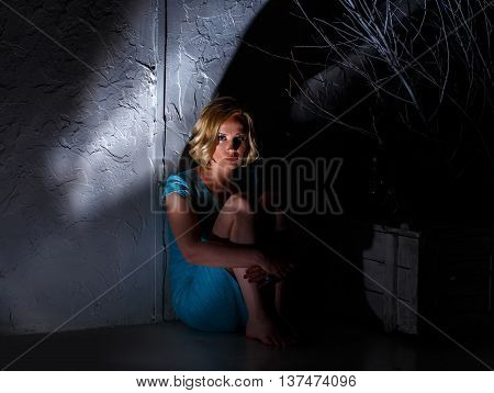 Young Woman In Blue Dress Sitting In Dark Horrible Place