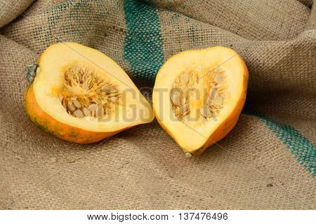Organic Raw acorn squash halves with seeds on burlap