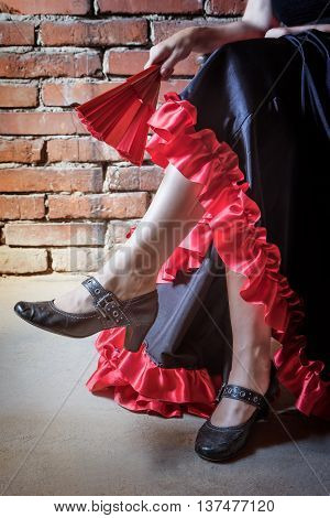 Close up view of leg of woman sitting on a chair and dressed in costume of Flamenco dancer with an closed red and black fan. The photo has deliberately darkened edges. Vertically.