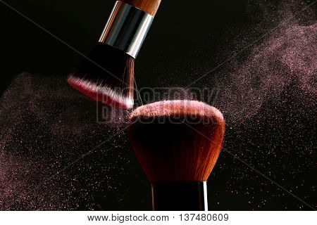Makeup brushes with flying powder on black background