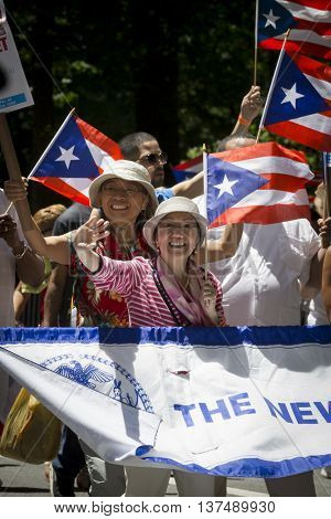 NEW YORK - JUNE 12 2016: Participants in the 59th annual National Puerto Rican Day Parade wave flags and celebrate as they march up 5th Avenue in New York City on June 12 2016.