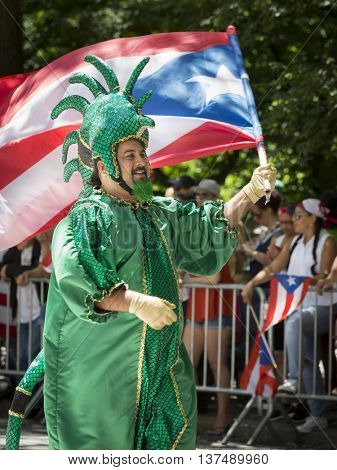 NEW YORK - JUNE 12 2016: A participant wearing a traditional carnival costume in the 59th annual National Puerto Rican Day Parade marches with a Puerto Rican flag on 5th Ave in NYC, June 12 2016.