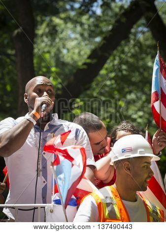 NEW YORK - JUNE 12 2016: Participants in the 59th annual National Puerto Rican Day Parade wave flags and celebrate on floats from along 5th Avenue in New York City on June 12 2016.