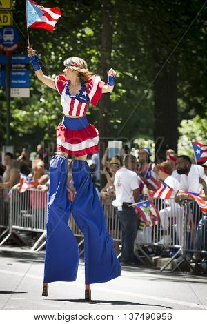 NEW YORK - JUNE 12 2016: A woman dressed in the red, white, and blue pattern of the Puerto Rican flag walks on stilts in the 59th National Puerto Rican Day Parade on 5th Ave in NYC on June 12 2016.