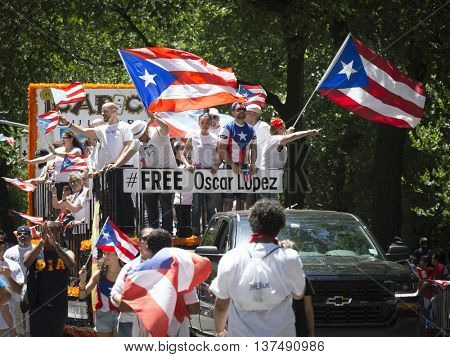 NEW YORK - JUNE 12 2016: Supporters of imprisoned nationalist Oscar Lopez Rivera on the FreeOscarLopez float wave Puerto Rico flags in the 59th National Puerto Rican Day Parade in NYC June 12 2016.