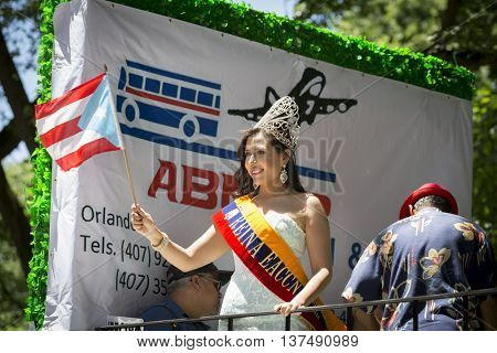 NEW YORK - JUNE 12 2016: A beauty queen from Columbia wearing a jeweled tiara waves the flag of Puerto Rico during the 59th National Puerto Rican Day Parade on 5th Ave in New York City, June 12 2016.