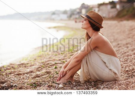 Calm woman sitting alone on a sand evening beach, sad and pensive