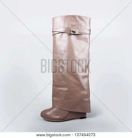 Ladies beige boots in a grey background