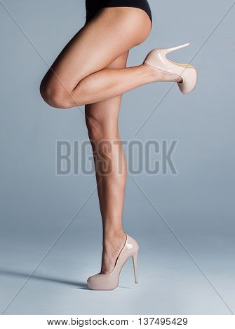 female legs in beige shoes over grey background