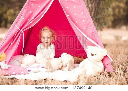 Cute baby girl 2-3 year old sitting playing with toys at back yard outdoors