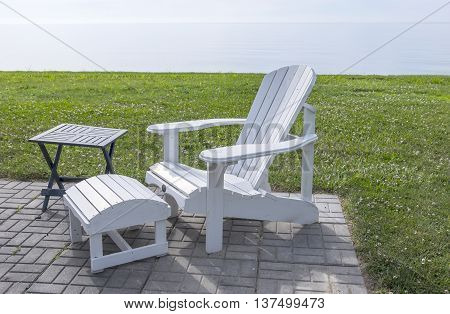 Serene Scene of a White Adirondack Chair by Lake Erie