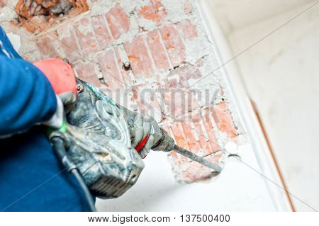 Handyman Using A Jackhammer To Distroy Concrete Interior Walls
