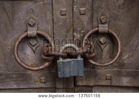 Steel padlock keeping the old door heck at the iron forged old door. Textured metal rusty background