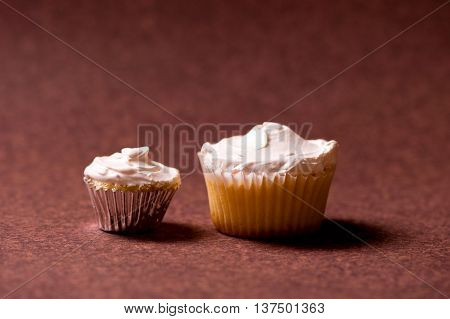 Two Vanilla Muffins With Sweet White Chocolate Cream Topping