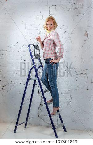 Sexy Blond Model With Lit Lantern Standing On Stepladder