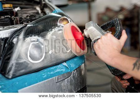 Automotive Engineer Polishing The Headlight Of A Car At Automobi