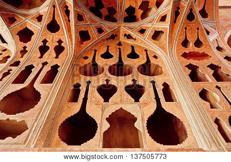 ISFAHAN, IRAN - OCT 18, 2014: Decoration of historical palace Ali Qapu with carved walls in musician theme on October 18, 2014. Safavid era palace Ali Qapu was built in early 17th century in Esfahan