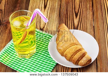 Glassful of lemon soda water with ice and tubule on green napkin. croissant wooden table