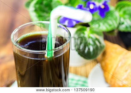 Glassful of black coffee with tubule croissant flowerpot on wooden table selective focus.