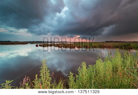 stormy sunset sky over wild lake in summer