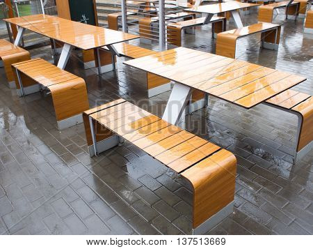 Wet tables outdoor cafe on the street in the rain