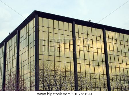 Modern mirror building with reflections of trees and the sky