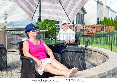 Elderly couple relaxing on an upmarket paved circular patio in the hot summer sun chilling out and enjoying the vacation in a comfortable armchair