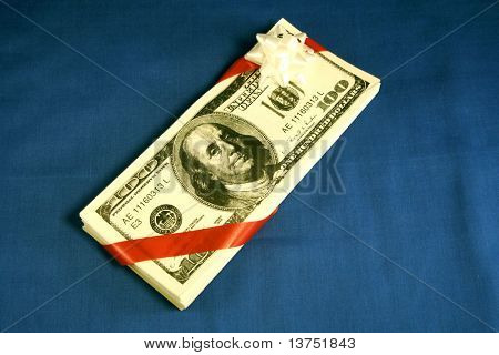 A stack of 100 dollar bills wrapped as a gift