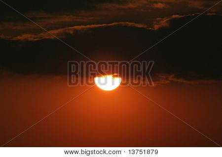 The sun just peeking below some clouds. Makes for a cool burning sky effect