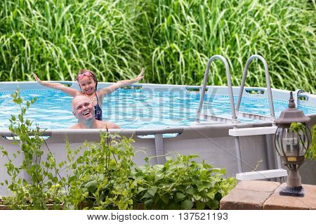 Happy father and his cute little five year old daughter in an above ground swimming pool laughing and smiling