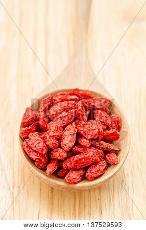 Wooden tablespoon of dried goji berries on wooden background.