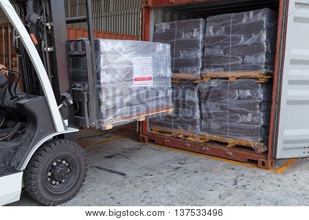 Forklift driver stacking of rubber briquette packs in to container box for export.