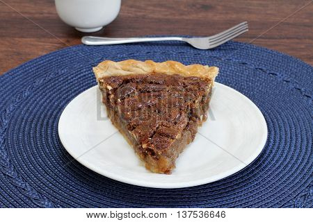 One slice of pecan pie point forward on a white plate. Close up copy space.