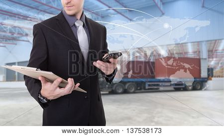 Manager checking plan at warehouse for Logistic Import Export background (Elements of this image furnished by NASA)