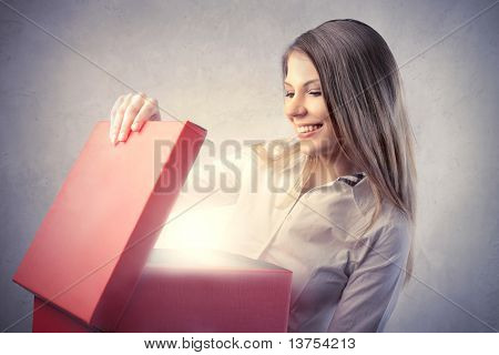 Happy beautiful woman opening a gift
