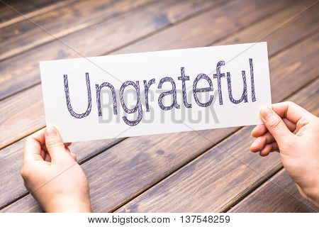 hands hold white paper with word ungrateful