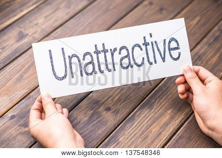 hands hold white paper with word unattractive