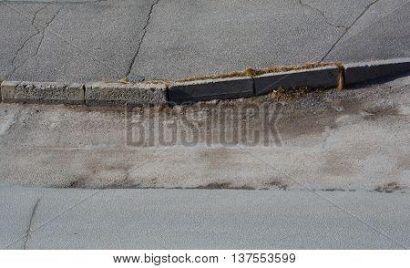 Sidewalk curb and road. Old asphalt with cracks