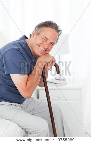 Retired man with his walking stick on his bed