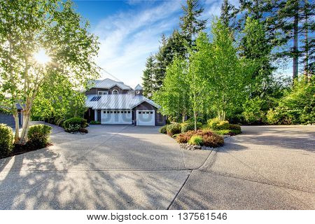 Modern House Exterior With Curb Appeal. View Of Garage And Spacious Driveway