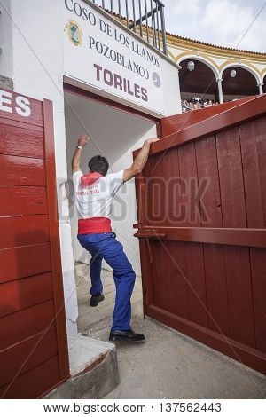 Pozoblanco Spain - September 23 2011: Man opens the bullpens door so that the bull goes out to the bullring of Pozoblanco Cordoba province Spain