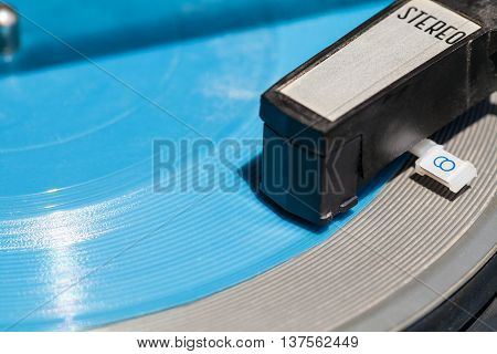 headshell of old turntable on blue flexi disc close up