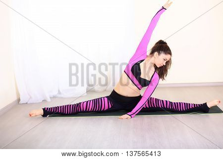 Sports and gymnastics. athletic woman doing aerobics gymnastics stretching exercises in a bright room. Beautiful SportWoman Dressed in colorful sportswear.