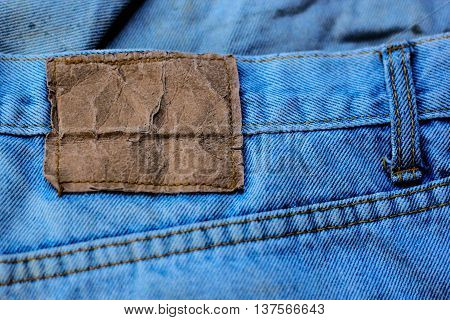 Blank label sewn onto blue jeans as background.