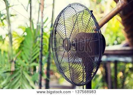 cooling, freshness and heat concept - close up of fan outdoors