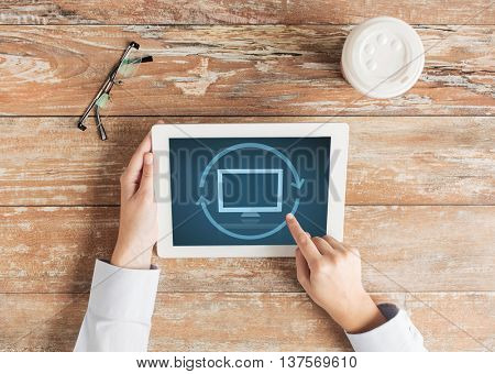 business, education, people and technology concept - close up of female hands pointing finger and restarting tablet pc computer at table