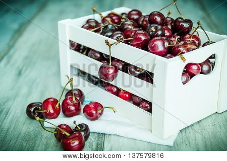 Cherries in a white wood crate over a wood background