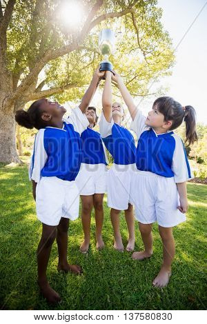 Front view of children soccer team celebrating a victory in park