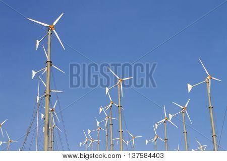 Wind driven generators turbines over blue sky